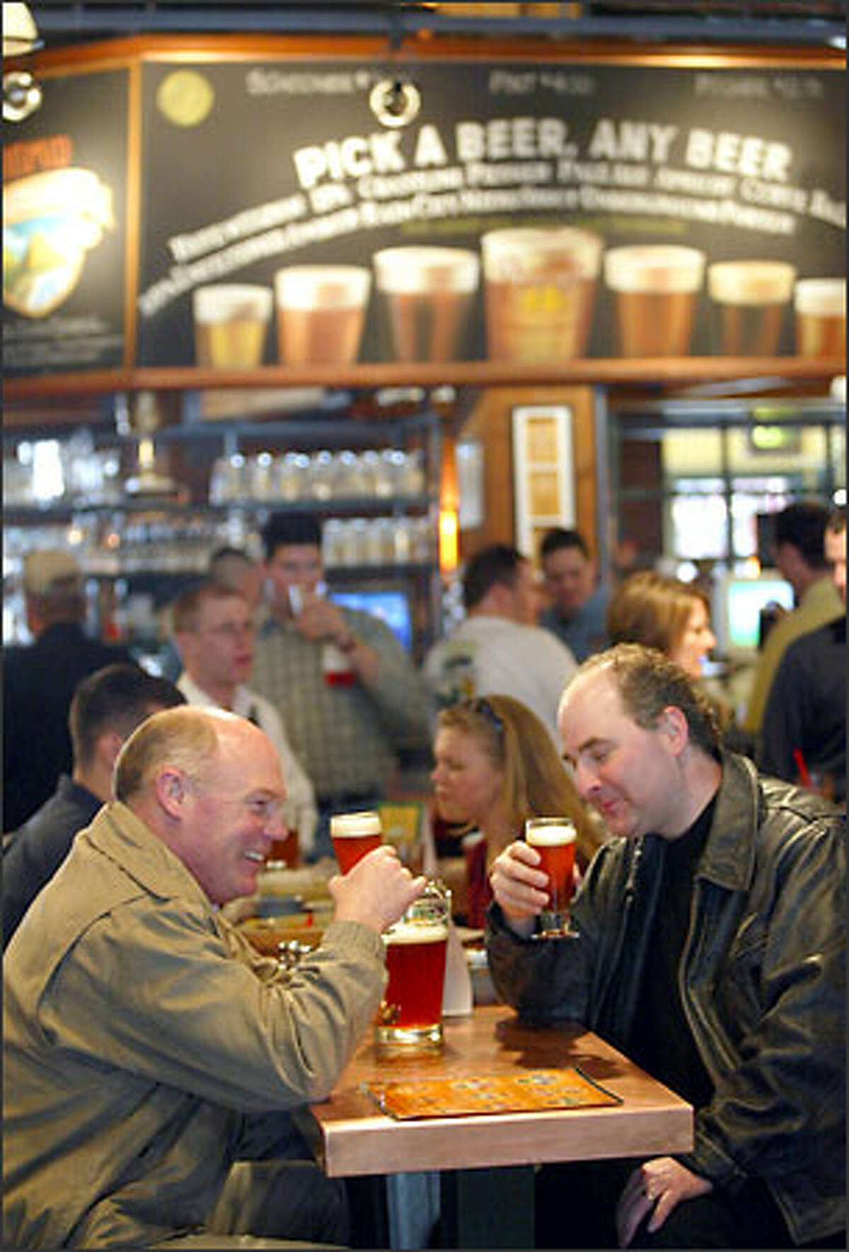 Two beer lovers share a pitcher at the Pyramid Alehouse across the street from Safeco Field before a Mariners game. Pyramid insists the brew pub's location is more luck than planning.
