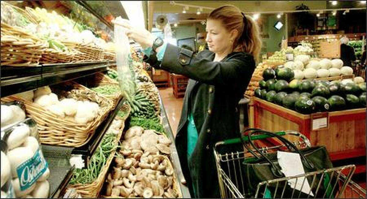 Cassie Menninga shops at the Whole Foods Market on Northeast 64th Street in Seattle. The company plans three larger stores in the Puget Sound area.