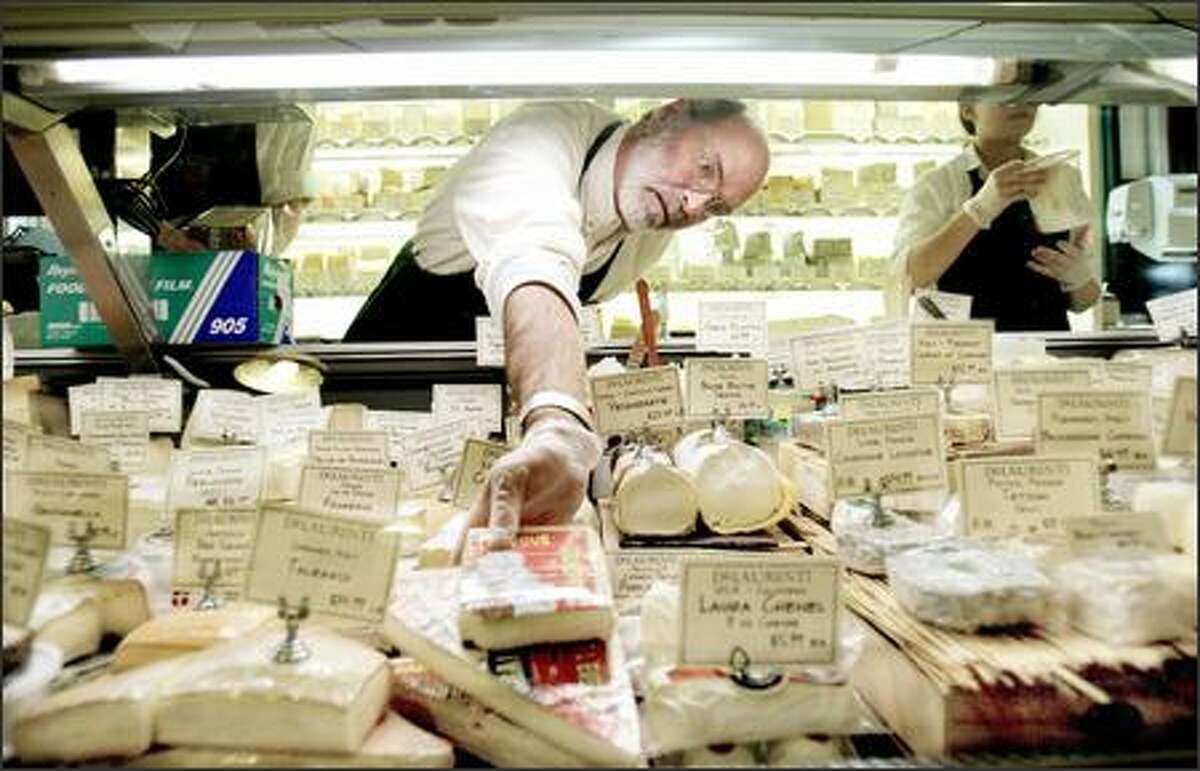 Brad Morris places cheese back in the case at DeLaurenti Specialty Food & Wine. The Pike Place Market shop, which carries 300 cheese varieties, is the sponsor of this weekend's cheese festival.