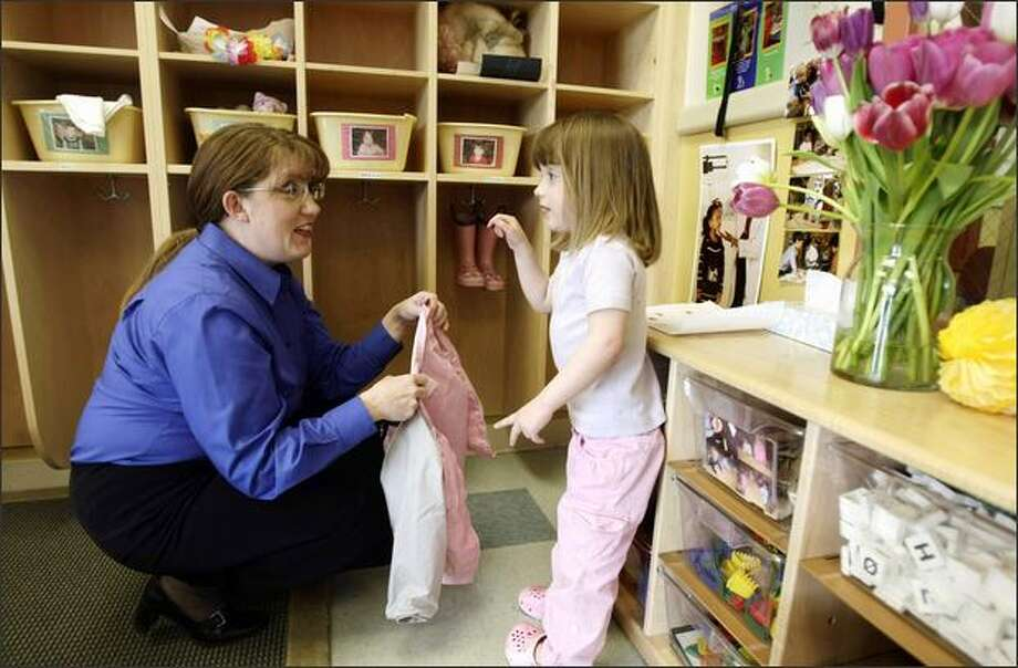 Cecilia Phillips, 3, shows her mom, Lorraine Lewis Phillips, a tulip Friday at Bright Horizons child care center. Phillips was picking up her children after a day at office. The attorney works at Keller Rohrback in Seattle. Photo: Andy Rogers, Seattle Post-Intelligencer / Seattle Post-Intelligencer