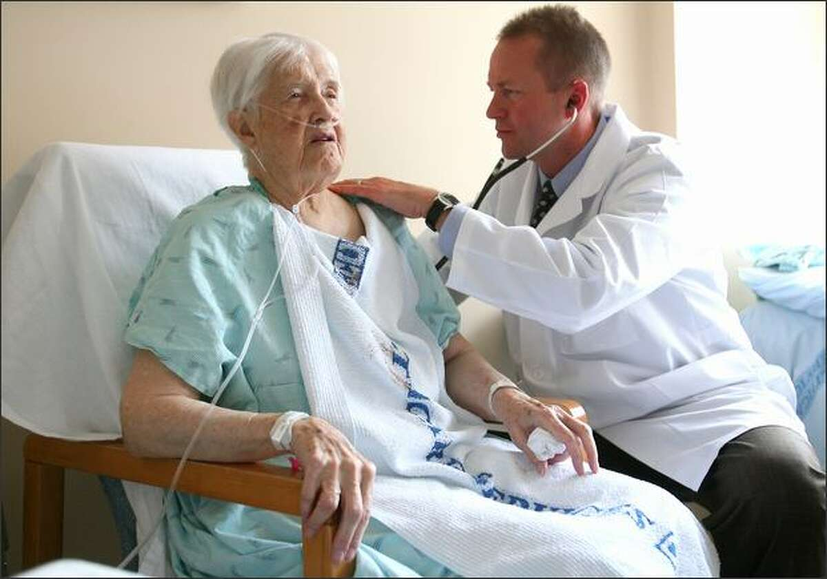 Dr. Per Danielsson, a hospitalist since 1996, examines Sister Anne Heger, 92, on Friday at Swedish Medical Center.