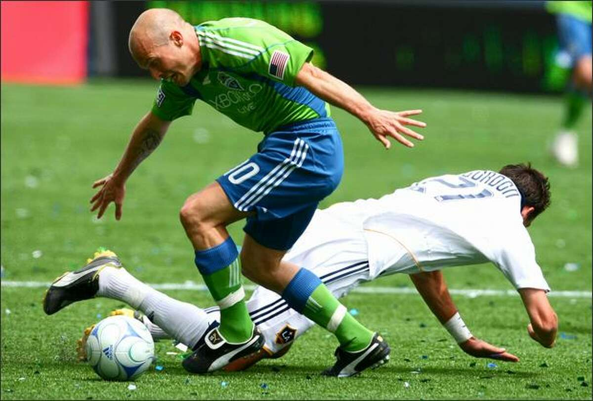Seattle Sounders player Freddie Ljungberg tangles with Los Angeles Galaxy player Alan Gordon (21) on Sunday during the first half at Qwest Field in Seattle.