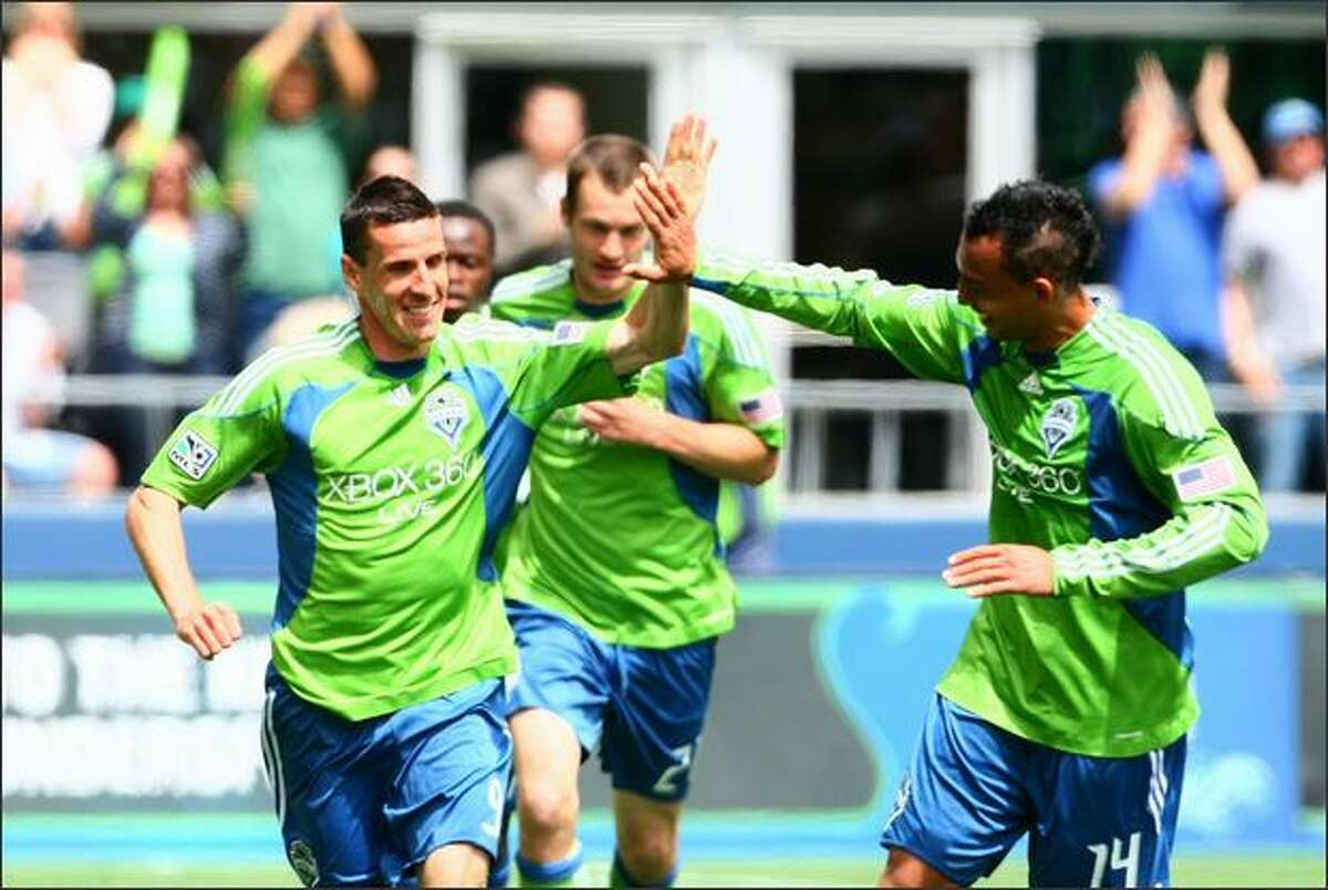 Seattle Sounders player Sebastien Le Toux gets congratulated after a goal by teammate Tyrone Marshall (14) against the Los Angeles Galaxy on Sunday during the first half at Qwest Field in Seattle.