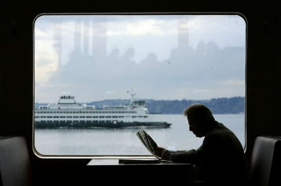 A passenger reads a newspaper aboard the M/V Tacoma as the boat sails to Seattle from Bainbridge Island on Wednesday April 29, 2009. Photo: Joshua Trujillo, Seattlepi.com / seattlepi.com