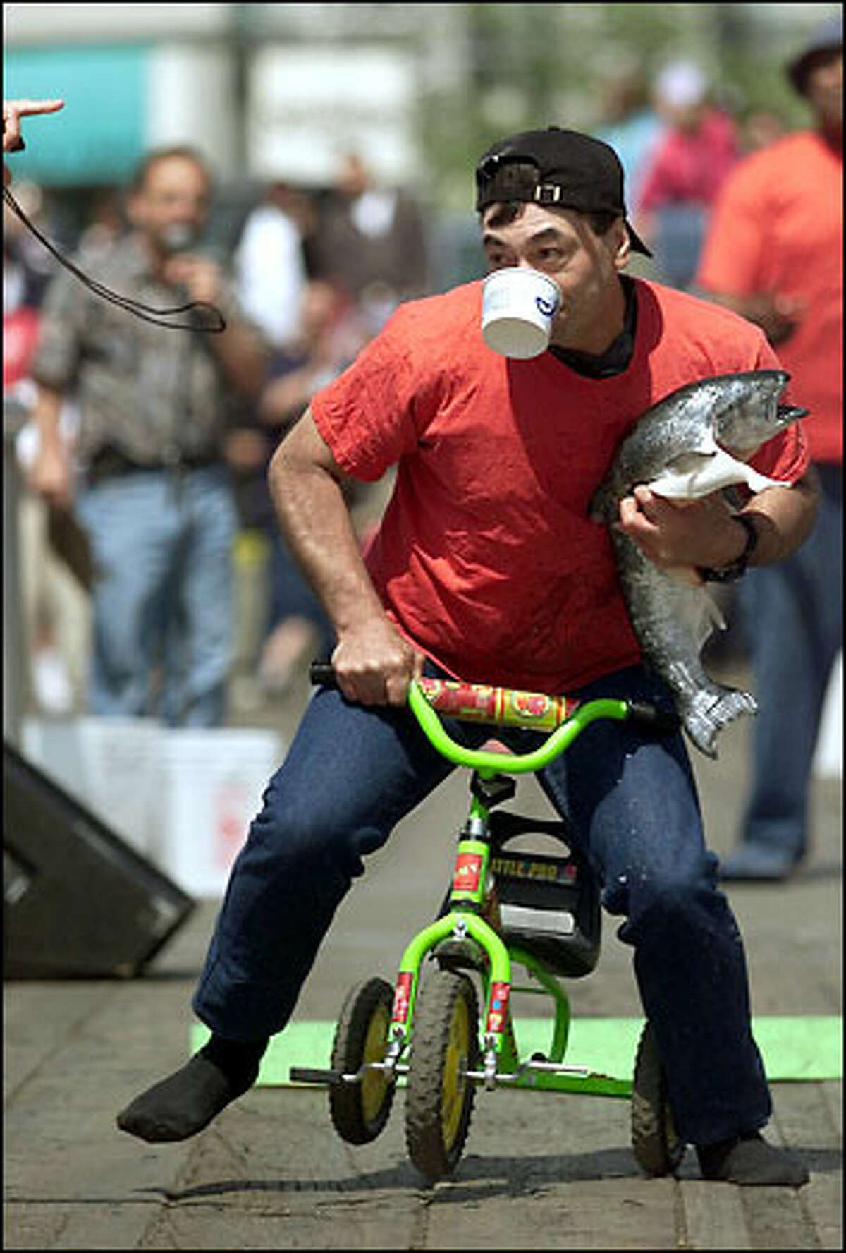 Mike Wolford takes part in an unusual tricycle race yesterday as part of Ivar's Waterfront Triathlon, which is part of the Seattle Maritime Festival. A greased salmon relay and oyster basketball were the other two events in the triathlon. The festival on Seattle's waterfront will conclude tomorrow with tugboat races beginning at 1 p.m.