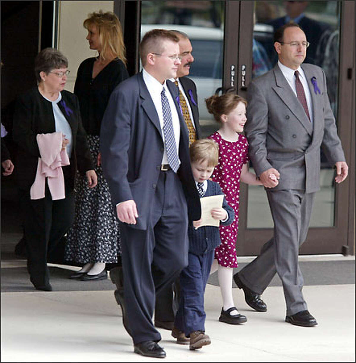 The children of Crystal Brame, David, 5, and Haley, 8, are escorted from their mother's funeral at Chapel Hill Presbyterian Church in Gig Harbor by unidentified family and friends. They are followed by their maternal grandmother, Patty Judson, left. Crystal Brame died May 3, a week after being shot in the head in a shopping center parking lot by her husband, Tacoma Police Chief David Brame, who then killed himself.