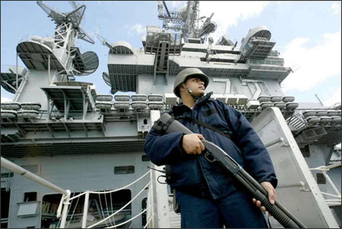 Petty Officer 3rd Class Jose Rodriguez guards the USS Abraham Lincoln yesterday. Naval Station Everett might be at risk in this base-closure round.