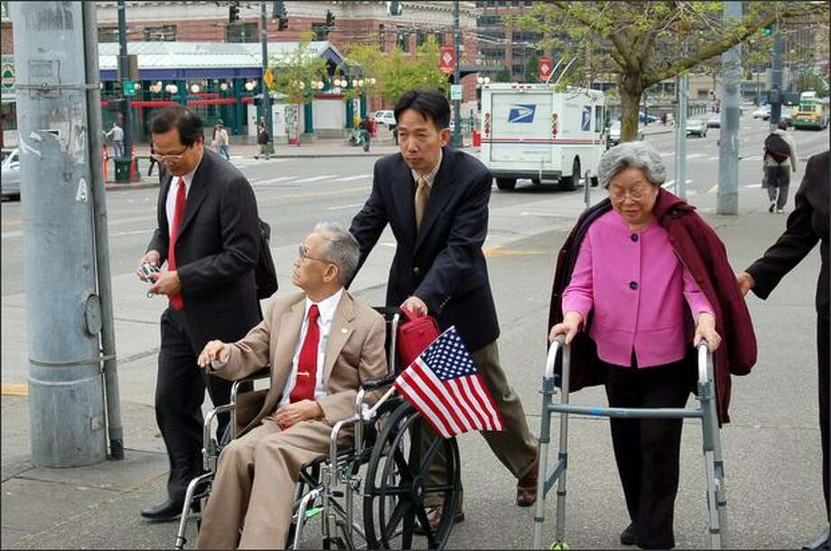 Mac Shin, in wheelchair, was honored Saturday for fighting the Japanese occupation of Vietnam in World War II. Disabled by a stroke, Shin is accompanied on Jackson Street by his wife Rose, with walker, and officials from the Embassy of Vietnam Nguyen Tien Minh, left, and Nguyen Ba Long, pushing the wheelchair. Photo: Tom Paulson, P-I / P-I