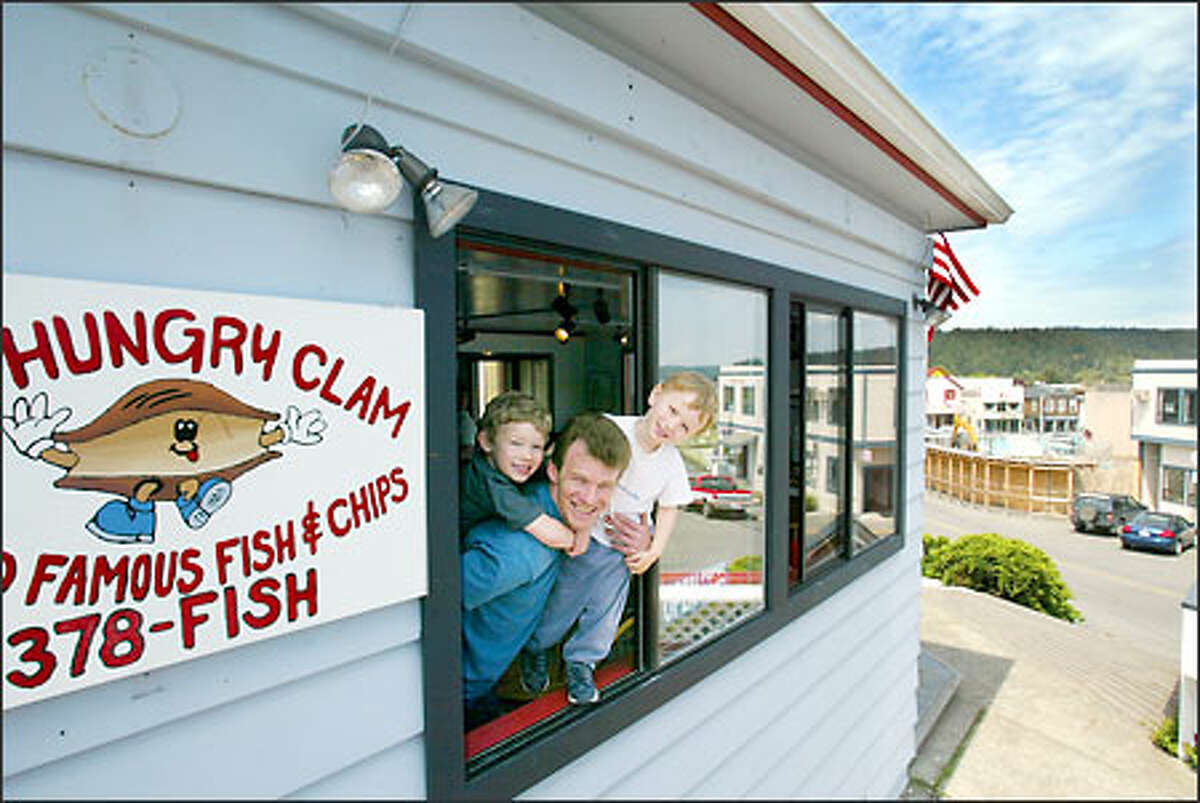 Stacy Brown -- with his sons, Sam, 5, and Dakota, 2 -- hangs out at the new location of The Hungry Clam, which he moved a block from the site that was burned down last year.
