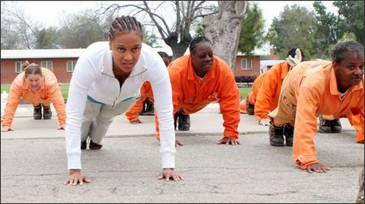 """This is not a shot that would make it onto """"America's Next Top Model"""" but if Tyra Banks were to go """"prison girl,"""" it would be. The model/talk-show host, left, does push-ups next to some of the ladies of the California Institution for Women in Chino, for an episode of """"The Tyra Banks Show."""""""