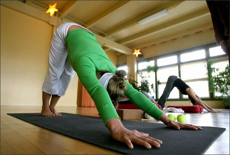The downward-facing dog, a staple starter move in yoga, can be performed easily. It is an instant energizer for yoga practitioners. Photo: Scott Eklund, Seattle Post-Intelligencer / Seattle Post-Intelligencer