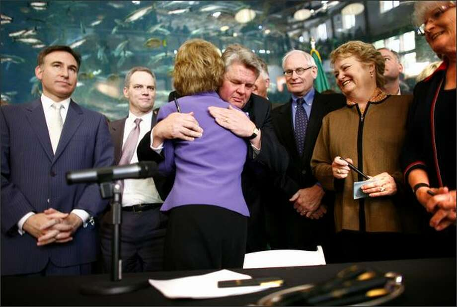 Washington State Governor Chris Gregoire is embraced by Seattle Mayor Greg Nickels after the governor signed Senate Bill 5768, authorizing funding for a tunnel to replace the earthquake-damaged Alaskan Way Viaduct on Tuesday. The bill commits $2.8 billion in state money to help build the tunnel. The removal of the viaduct will dramatically change the Seattle waterfront. Photo: Joshua Trujillo, Seattlepi.com / seattlepi.com