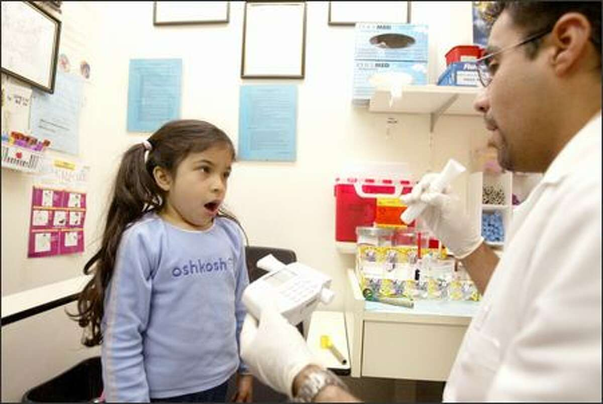 Technician Luis Fernando Luna prepares to administer an asthma test to Helen Rubio, 6, of White Center during Asthma Day at the SeaMar clinic.
