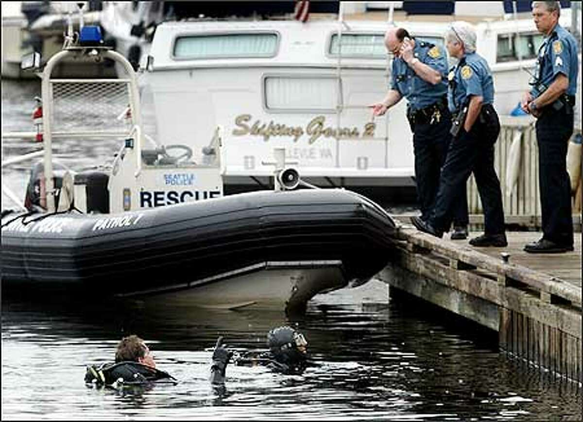 Rescue divers talk with officers on a dock after a man drove his car into Lake Union on Thursday at the Sunnyside Avenue North Boat Ramp next to the Puget Sound Yacht Club in Seattle.