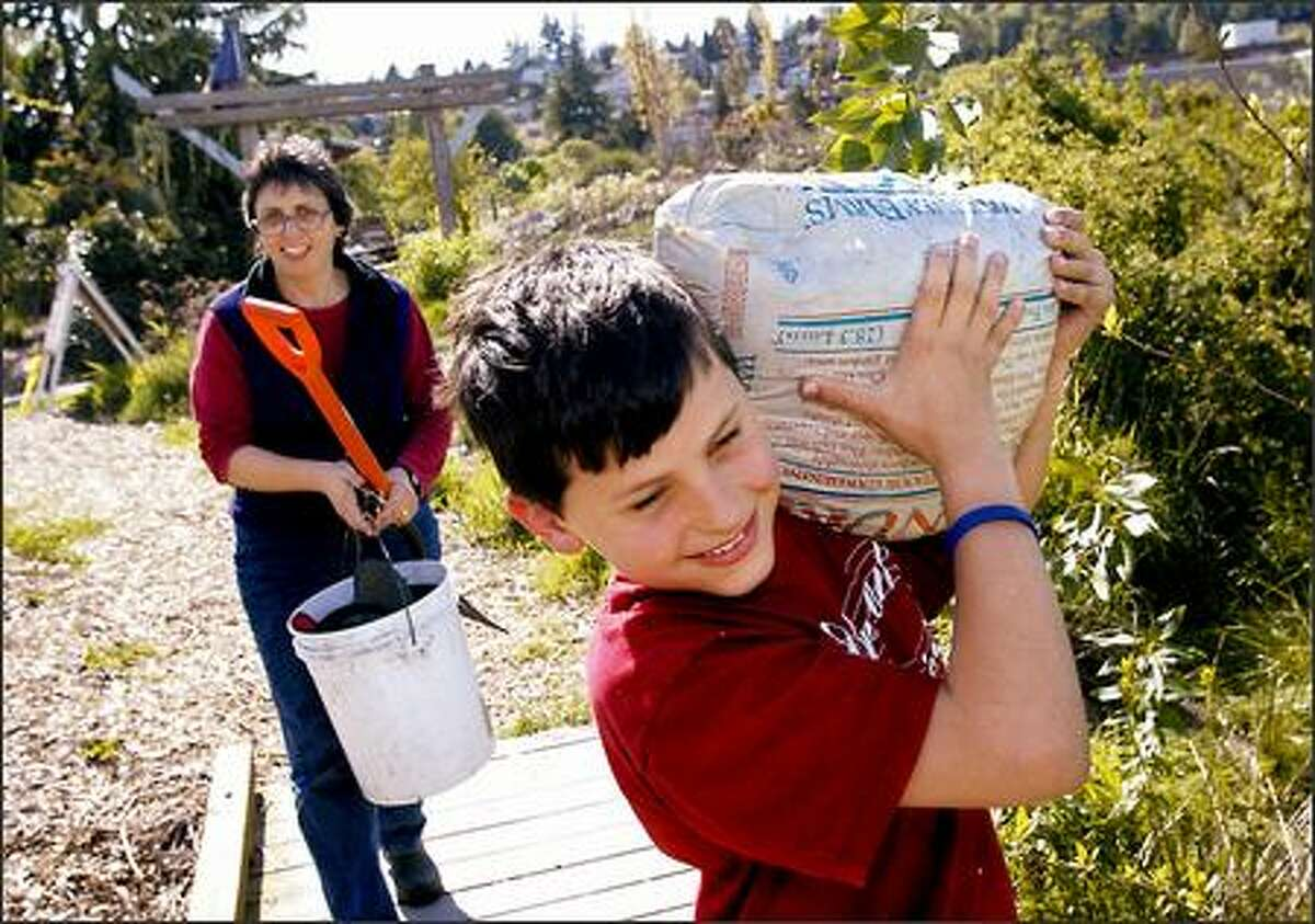 Christina Pfeiffer carries the tools while her son, Max, totes a bag of compost to their family garden at Magnuson Community Garden.