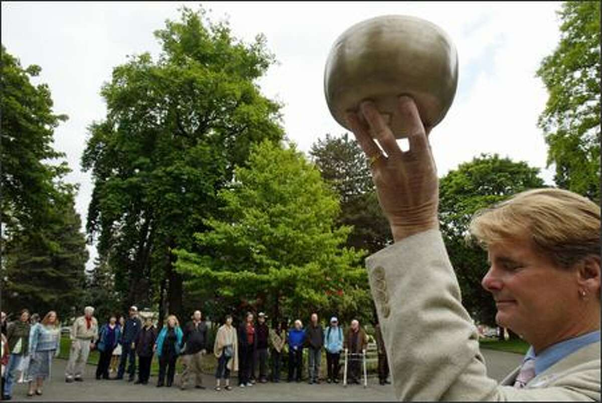 Richard Levy, senior minister of Seattle Unity Church, raises a Tibetan bowl that he rang to start the group's five minutes of silence at Denny Park on Sunday.
