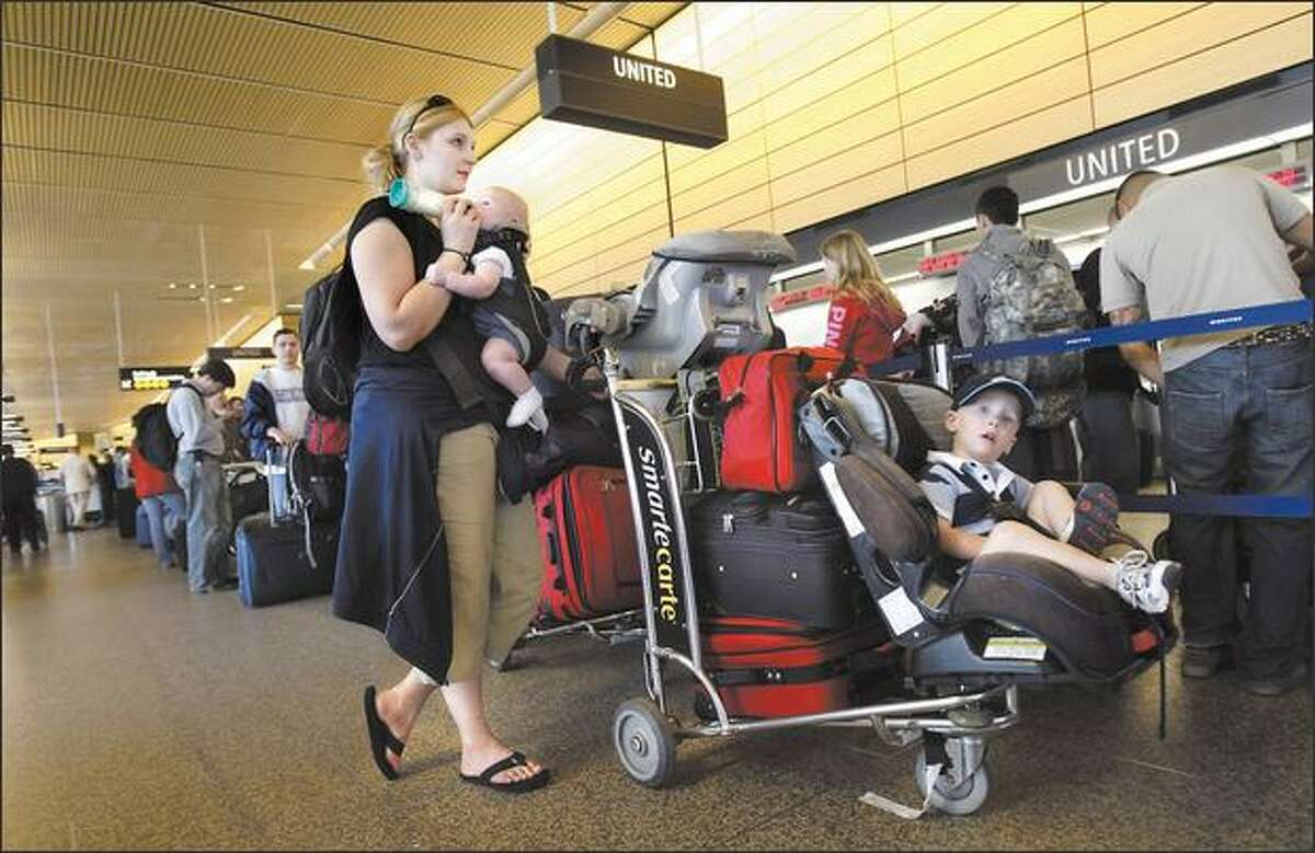 Two-year-old Devon Roeder has a thousand-yard stare as he waits in a long check-in line in his booster seat while his mother, Sandy, feeds his baby brother, Nathaniel, at Sea-Tac Airport on Thursday.