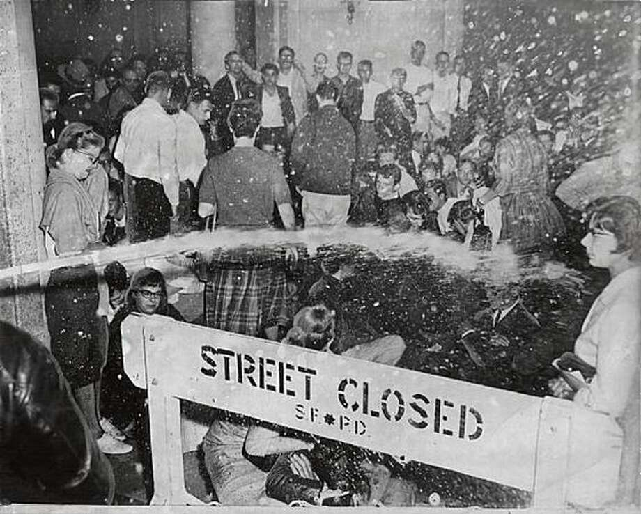 "Water from a fire hose pours over a barricade onto protesters in the street during the ""Black Friday"" protests in San Francisco on May 13, 1960. Photo: San Francisco Chronicle / San Francisco Chronicle"
