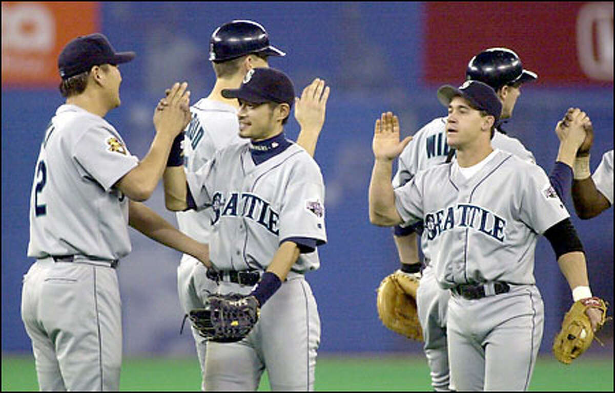 Seattle's Kazuhiro Sasaki, far left, and Ichiro Suzuki congratulate each other in the team lineup after completing a sweep of Toronto. Ichiro extended his hitting streak to 19 games.