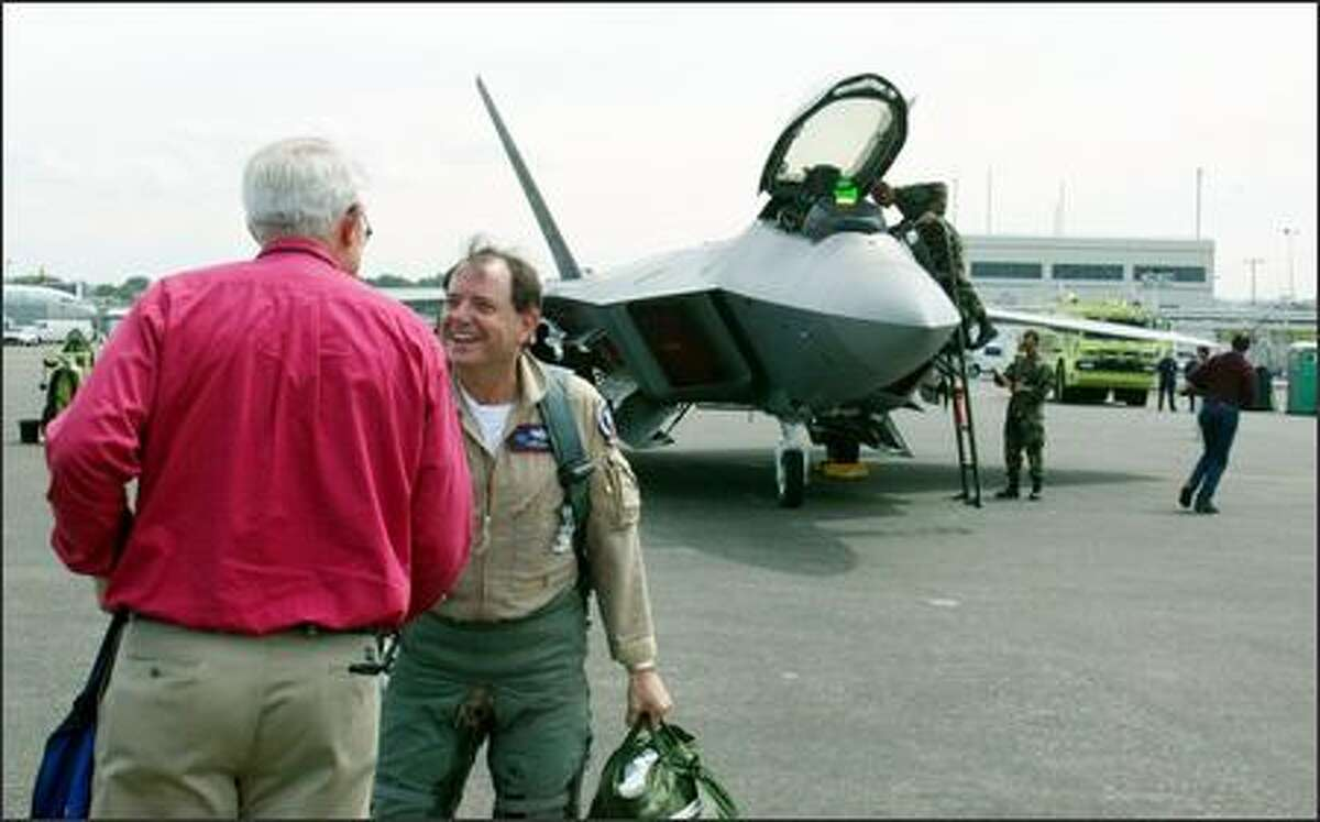 Boeing test pilot Randy Neville, facing camera, is greeted by Rich Nelson, Boeing test manager for the F-22 Raptor, after landing the advanced fighter.