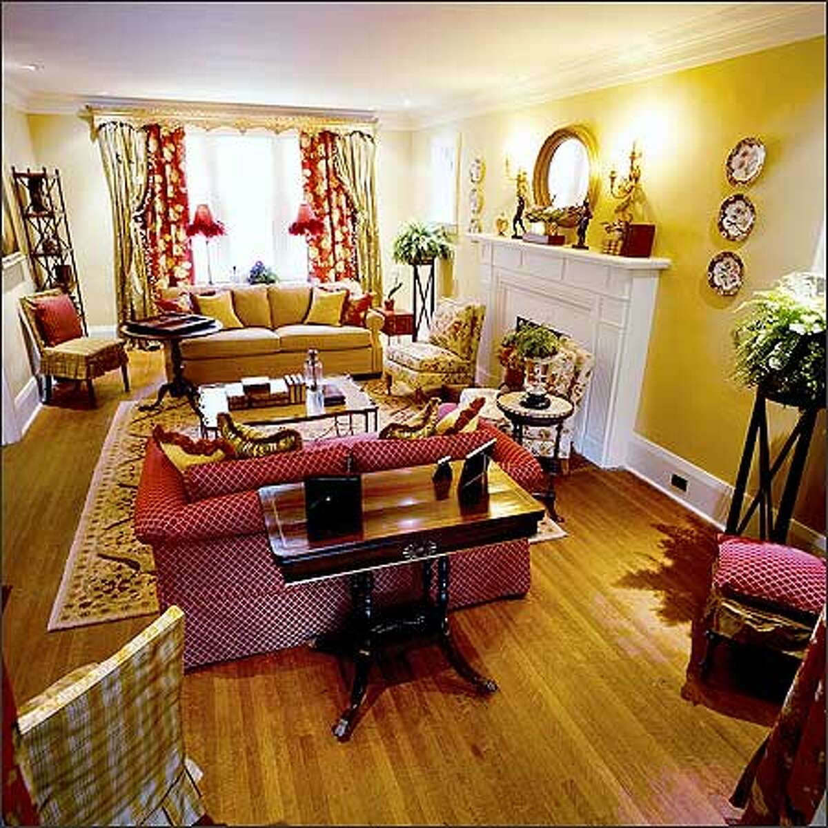 After: Creative lighting and a wonderful palette of reds, creams and yellows give this room a big boost of color and cherished antiques a new lease on life.