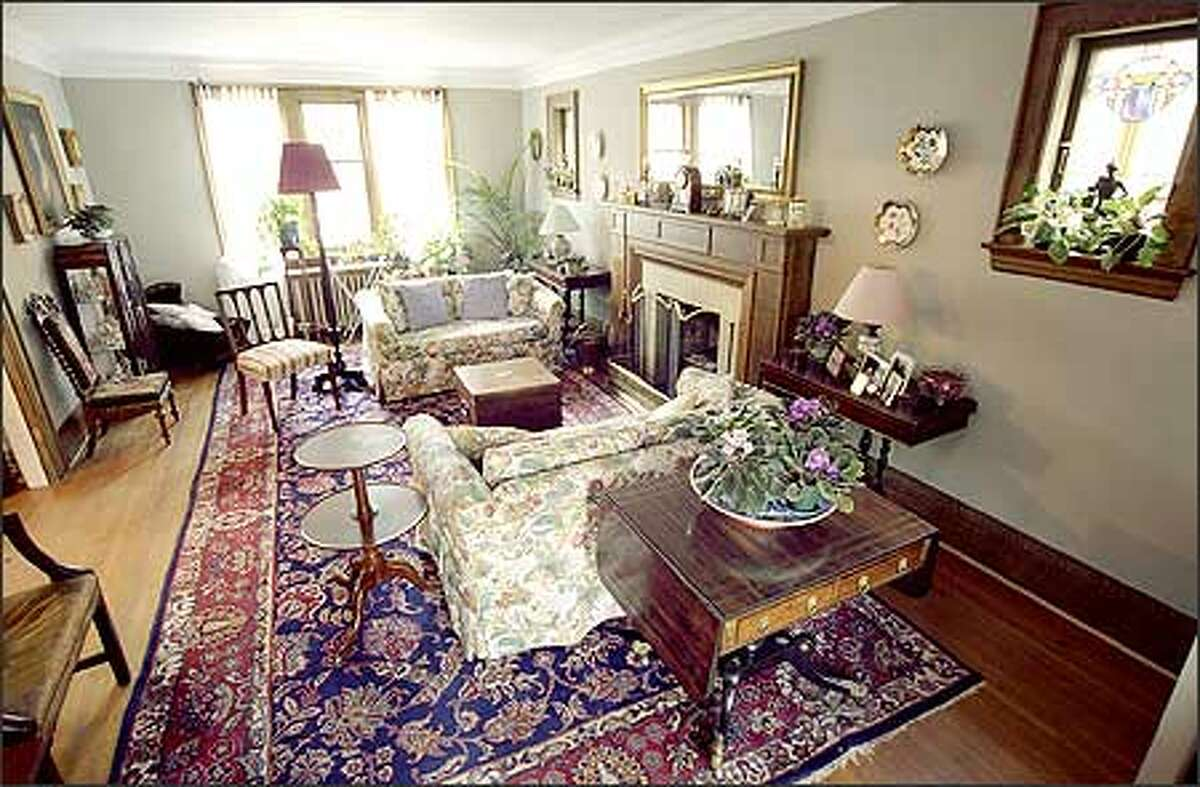 Before: In this living room, an abundance of antique furniture, an overpowering rug and dark woodwork around the fireplace combined to produce a dated, dim space.