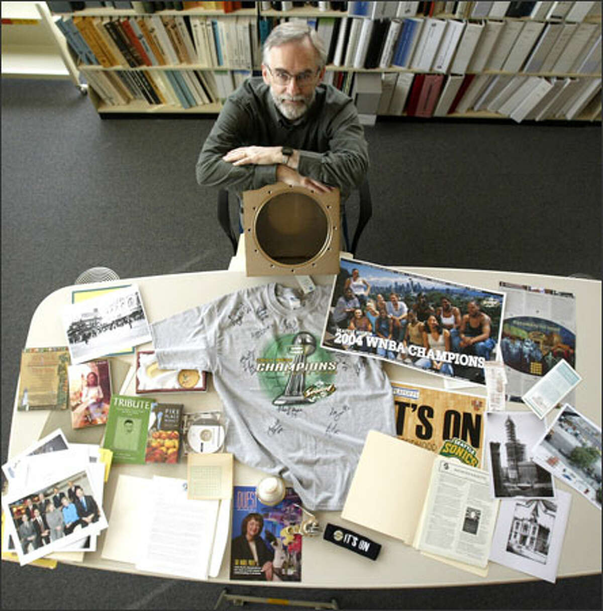 City Archivist Scott Cline has gathered Seattle memorabilia to be sealed in a stainless steel time capsule and buried under the new City Hall plaza today.