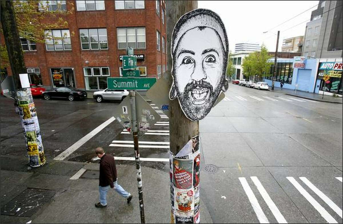 A drawing of a face is stuck on a telephone pole at the intersection of Summit Avenue and East Pine Street in Seattle. City leaders met to figure out how to maintain the character of the neighborhood.