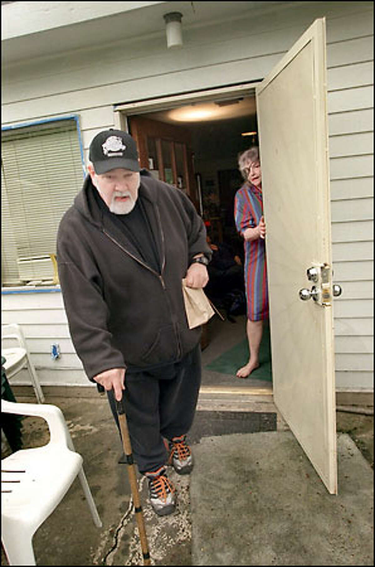 Brad Waugh, who has multiple sclerosis and diabetes and belongs to the Green Cross Cooperative, leaves with a bag of marijuana. JoAnna McKee holds the door.