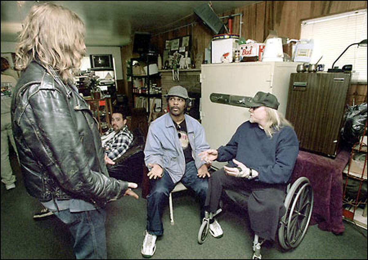 At the Green Cross Cooperative, from left, Colin Karvanek, Gabriel Rivas, Harry A. Jones Jr. and Frank Farkas Jr. discuss yesterday's Supreme Court marijuana ruling as they wait for their doses.