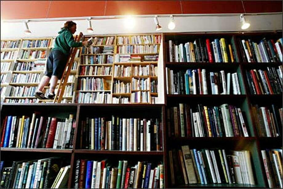 Customer Tina Bechler of Seattle browses the top shelves of used books at Bookworm Exchange, a used bookstore that opened recently in Columbia City. Photo: Dan DeLong, Seattle Post-Intelligencer / Seattle Post-Intelligencer