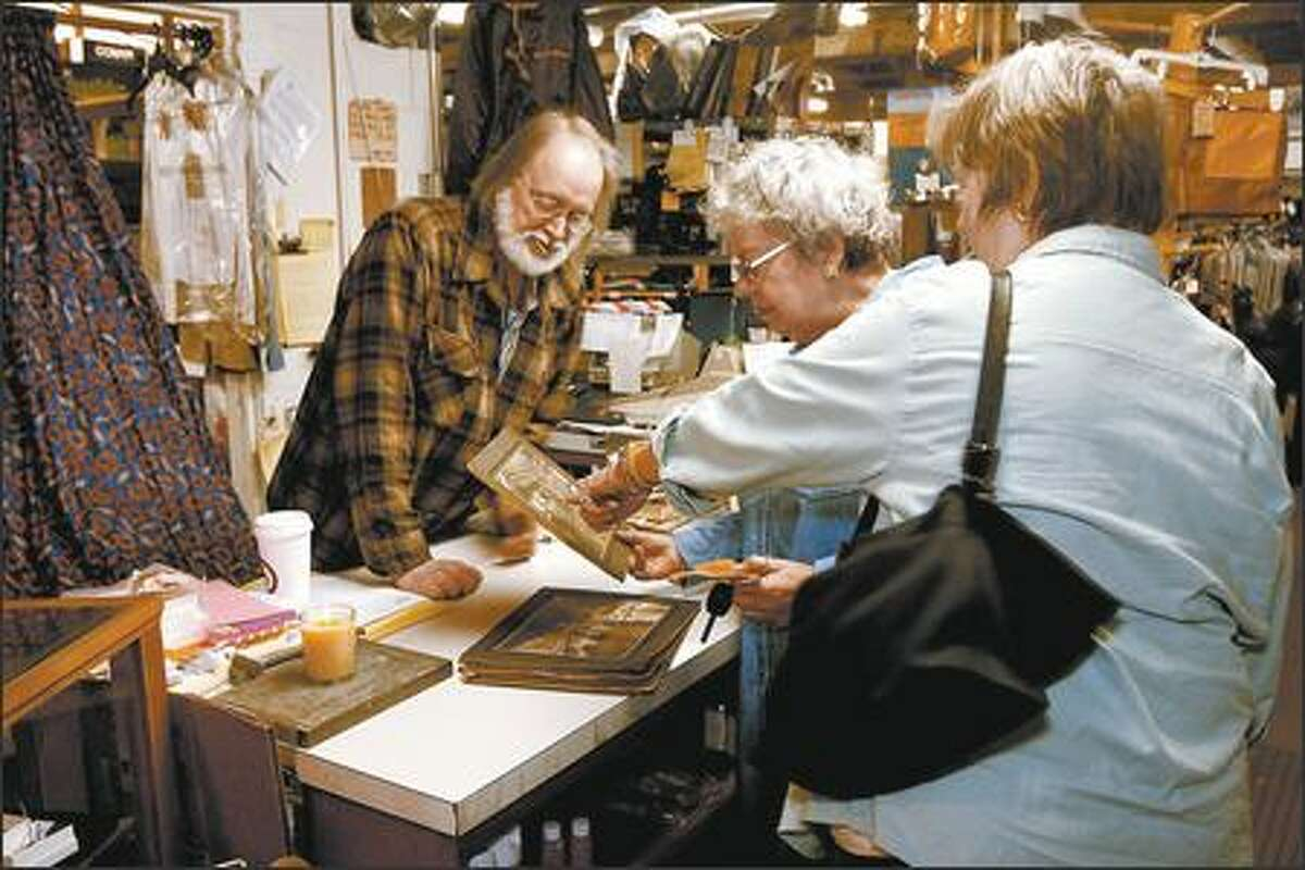 Larry Duncan, left, co-owner of Duncan & Sons, on Monday shows photos of the store from its glory days in the early 1900s to Sara-Jane Bellanca and Martha Gordon, right, longtime friends who stopped by to say goodbye. The store will close May 31.