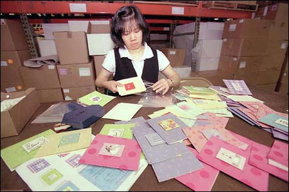 Yuk Ho Kwong puts the finishing touches on greeting cards at Madison Park Greetings in Seattle. The company originally was known as Lucy and Me.