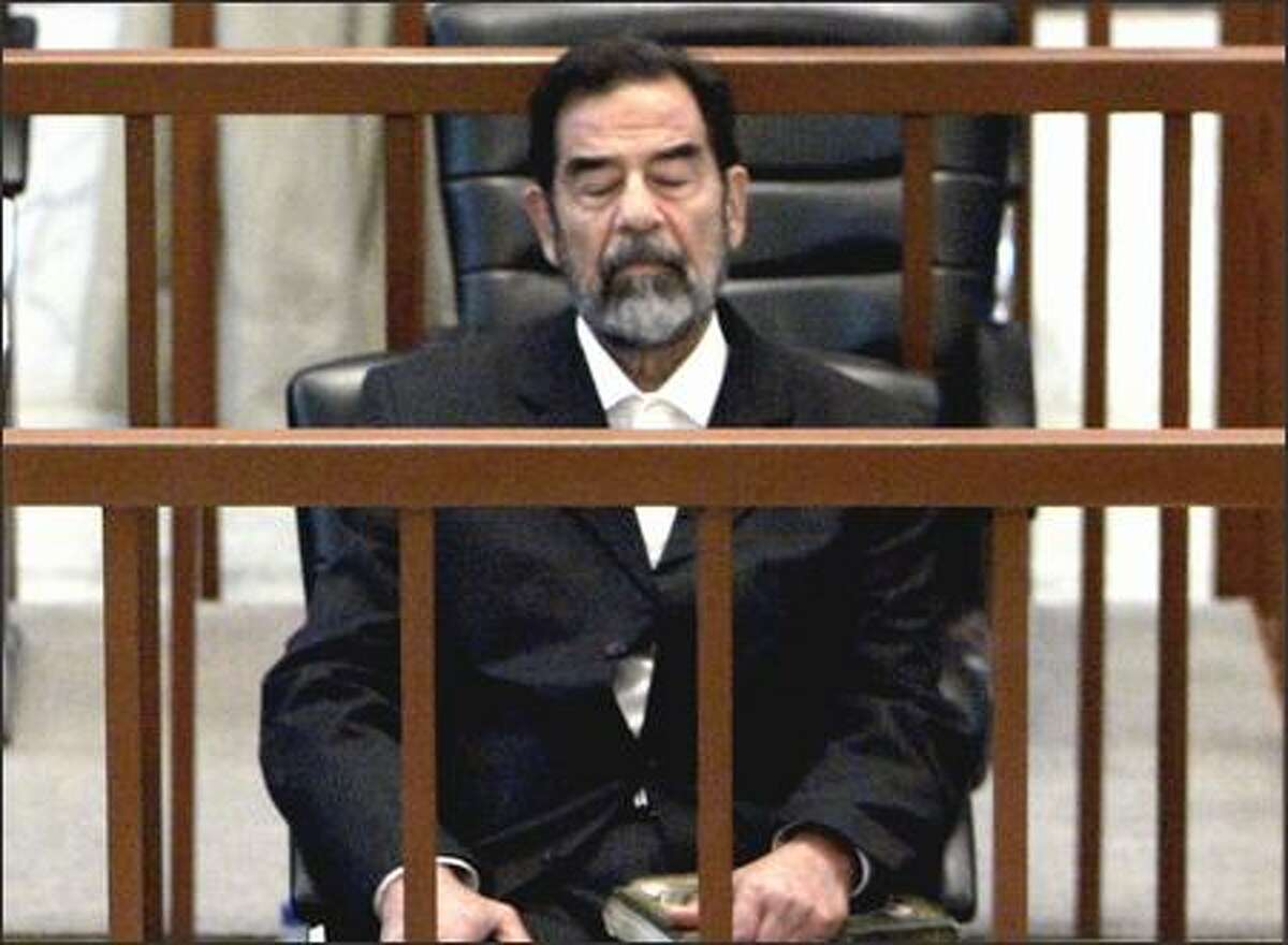 Former Iraqi President Saddam Hussein listens as Chief Judge Raouf Abdel-Rahman formally charges him Monday in Baghdad with murder, torture and the illegal arrests of 399 people during the 1980s.