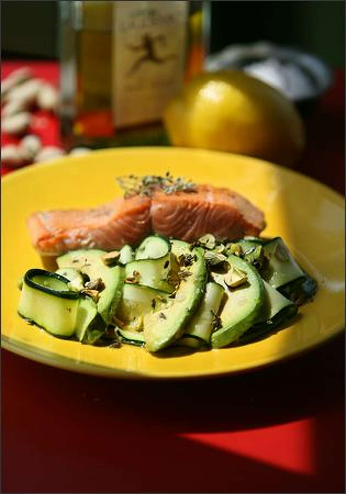 Zucchini Carpaccio With Avocado, Lemon Thyme and Pistachio Oil is served with a side of grilled salmon.
