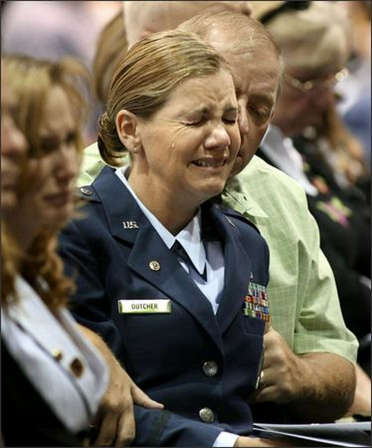 Air Force Reserve Capt. Teresa Dutcher is comforted by her husband, Jeffrey Dutcher, at a memorial for her son, Cpl. Michael Avery Pursel, and five other soldiers killed in Iraq.