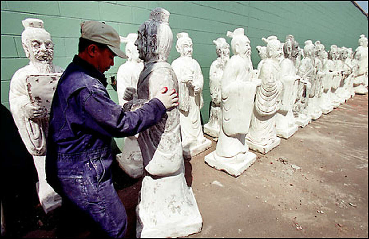 Son Huynh moves one of 73 statues of a Chinese teacher and students outside the Golden Palace Seafood Restaurant in Rainier Valley. Widening of a driveway forced the statue's long march yesterday from one side of the building to the other at the restaurant at the 6700 block of Martin Luther King Jr. Way.