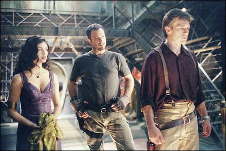 "Morena Baccarin as Inara, Adam Baldwin as Jayne and Nathan Fillion as Captain Malcolm ""Mal"" Reynolds in the new Fox science-fiction adventure series ""Firefly."""