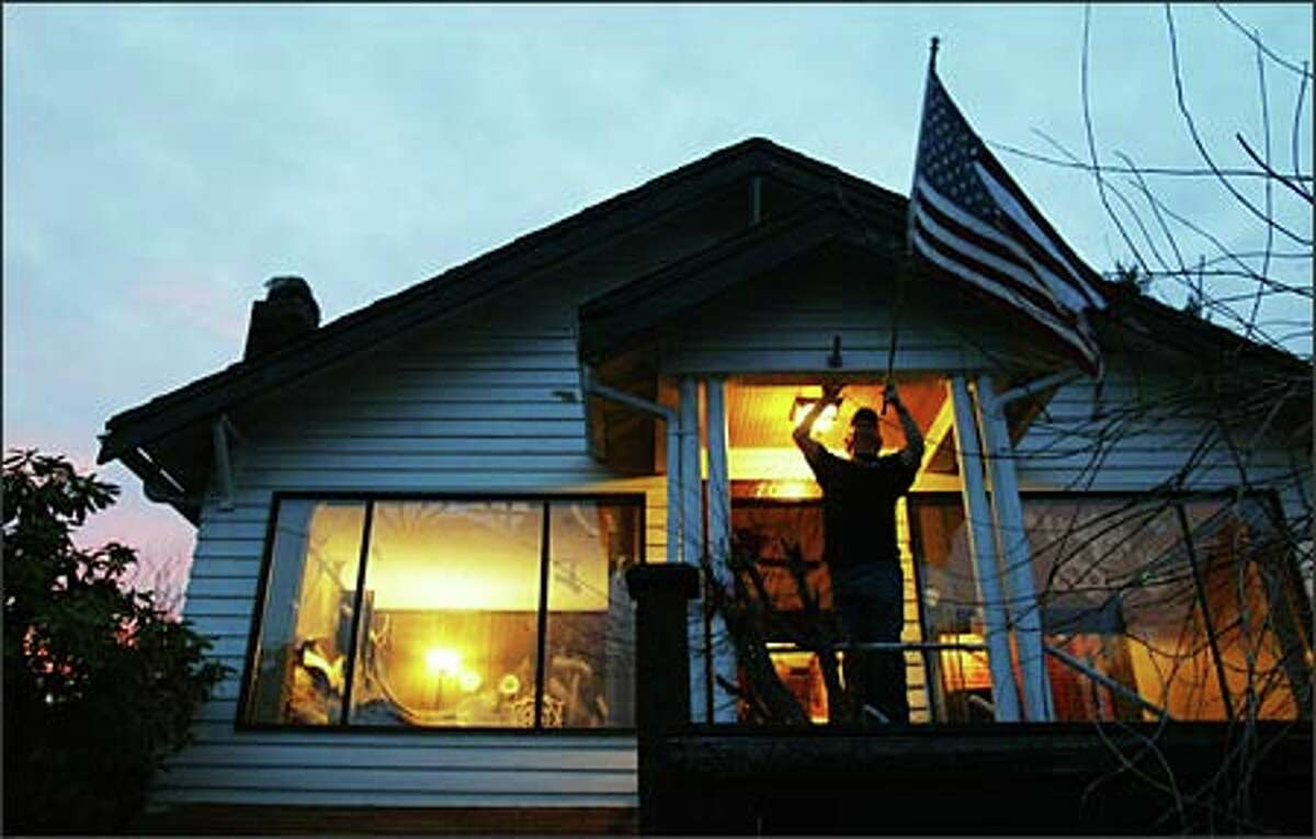 Tom Whyte takes down his flag on the night his family moved out of their Ballard home. Tom lost his job and they could no longer afford the mortgage payments.