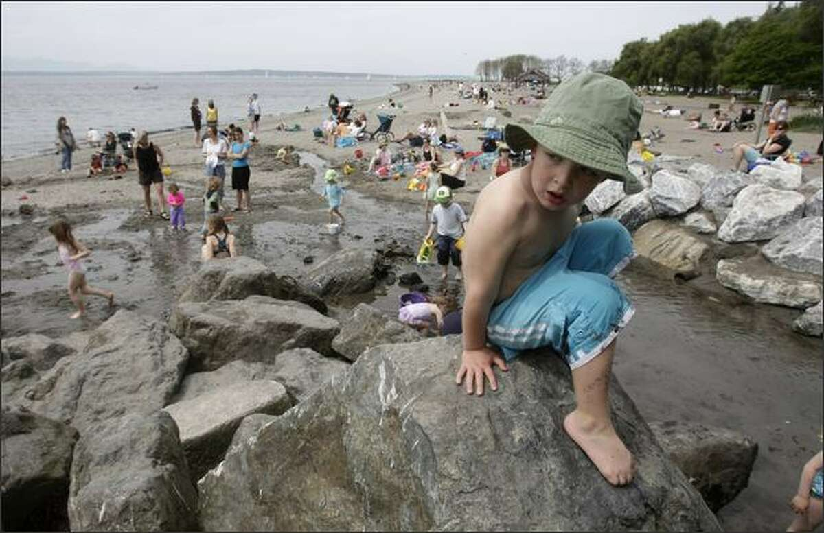 Carter Ely, 3, climbs the rocks by the creek Friday at Golden Gardens Park. Despite sometimes-overcast skies and a breeze, warm weather attracted many visitors to the beach. It will be warm again Saturday.