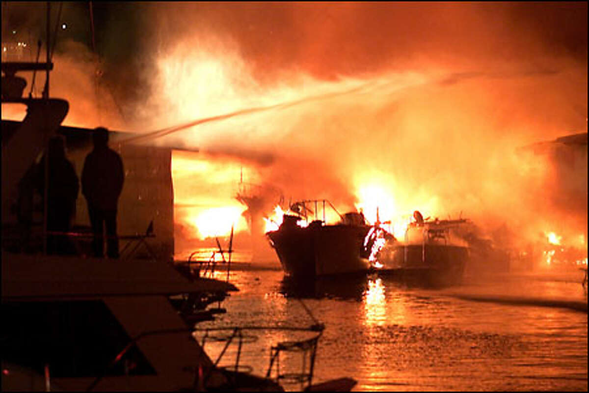 Firefighters battle an explosive series of fires at the Seattle Marina on North Northlake Way last night. Dozens of boats and yachts were destroyed, but there was no word of injuries.