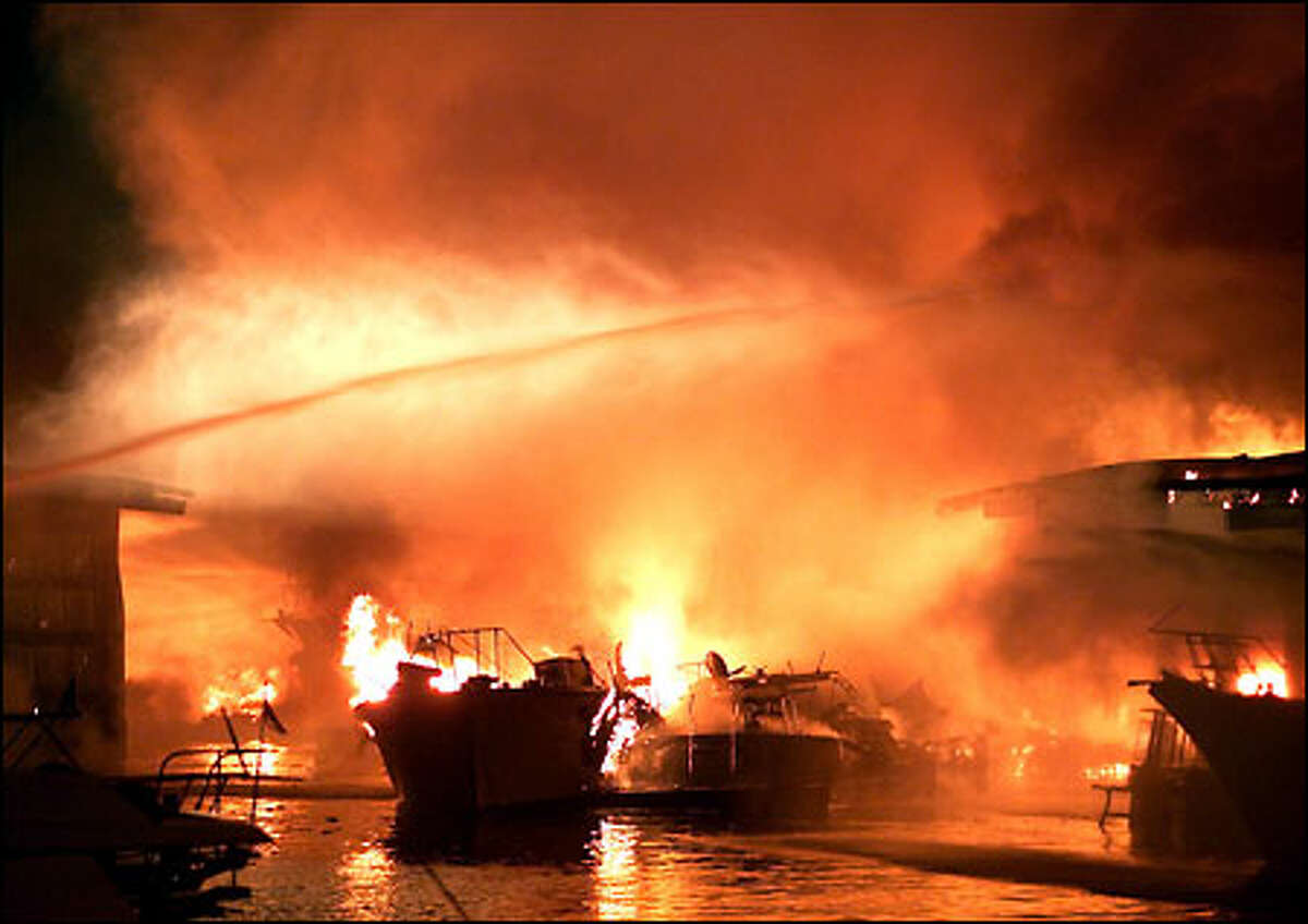 Firefighters battle an explosive series of fires at the Seattle Marina on North Northlake Way last night. Dozens of boats and yachts were destroyed, but there were no reported injuries.