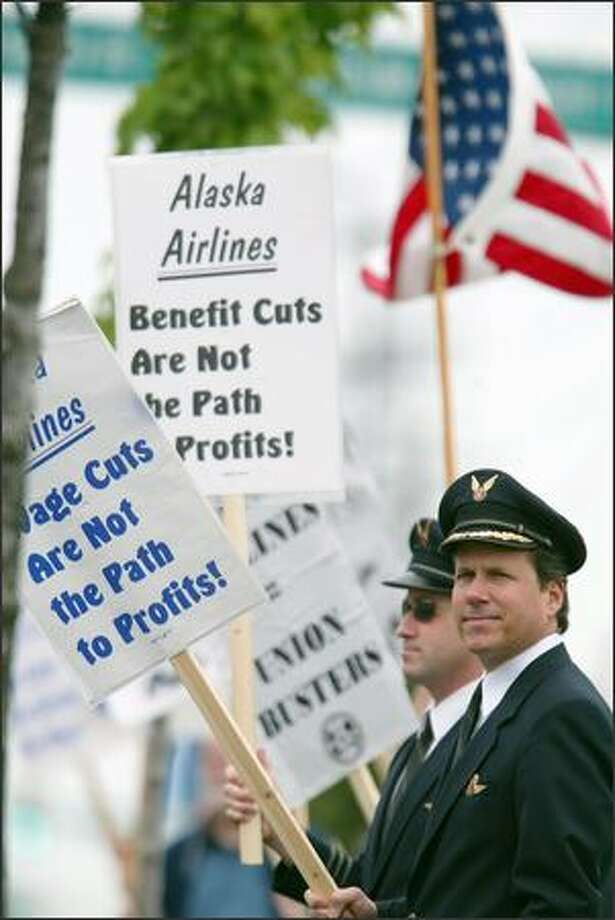 Alaska Airlines pilots Peter Barbin, left, and Glenn Vyskocic joined others picketing outside the annual shareholders meeting yesterday at the Museum of Flight. Employees are upset about layoffs and reduced pay. Photo: Paul Joseph Brown, Seattle Post-Intelligencer / Seattle Post-Intelligencer