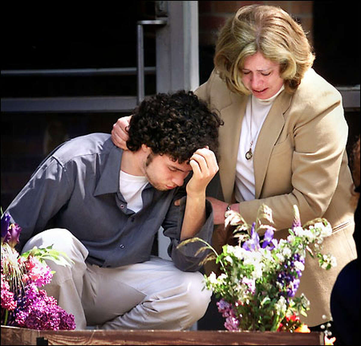 Mark Carr, stepson of James D. Holloway, and his mother, Judy Carr, Holloway's wife, mourn at Pacific Lutheran University yesterday.