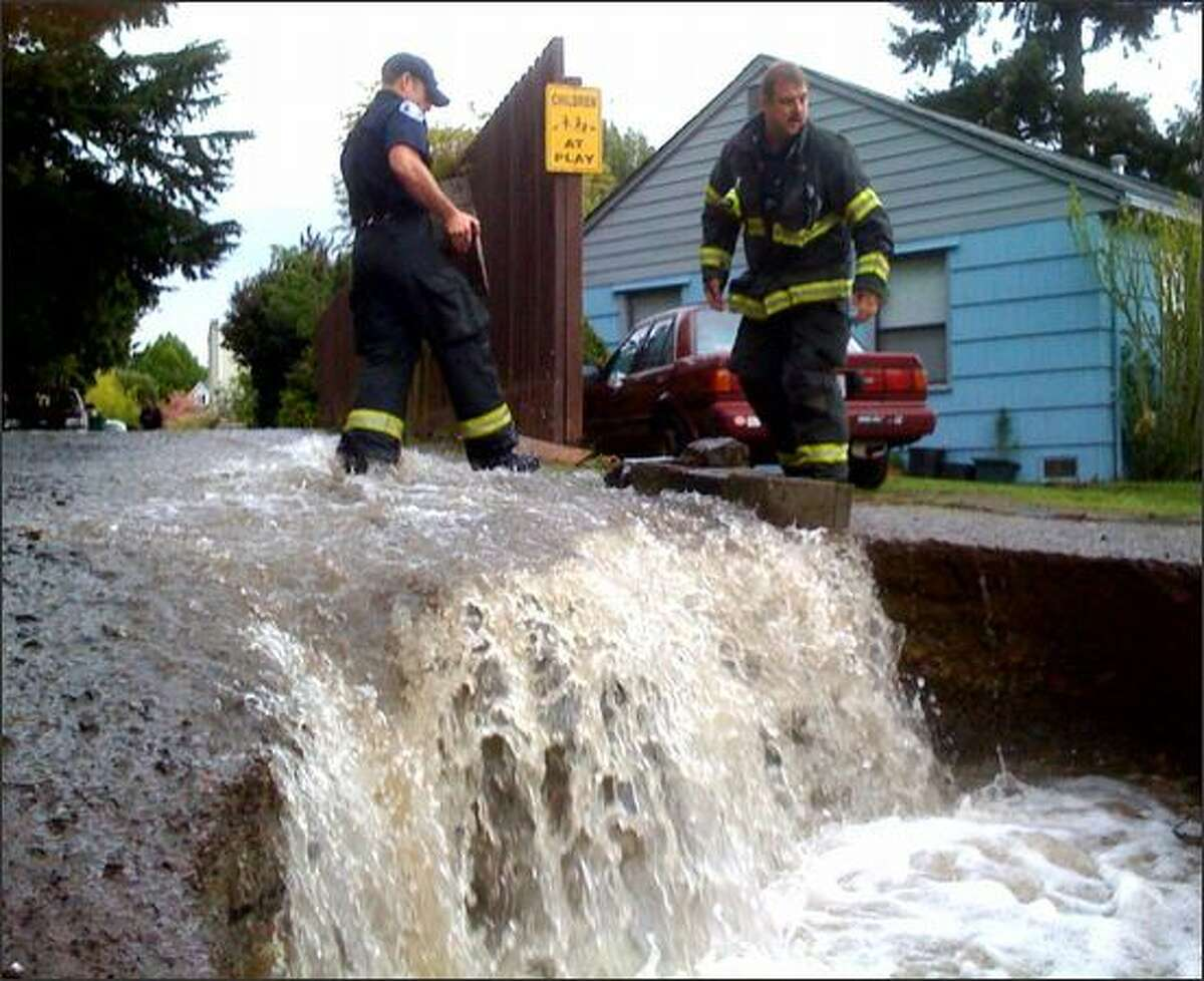 Seattle firefighters at the scene of a water main break in Ravenna.