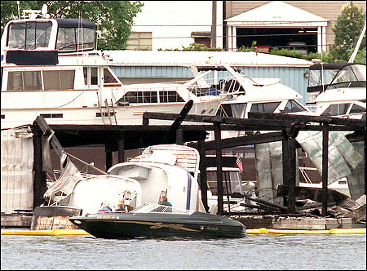 A man and three children in a small boat slowly cruise by the Columbia's stern sticking out of the water. The Columbia burned and sank during Friday night's fire on Lake Union.