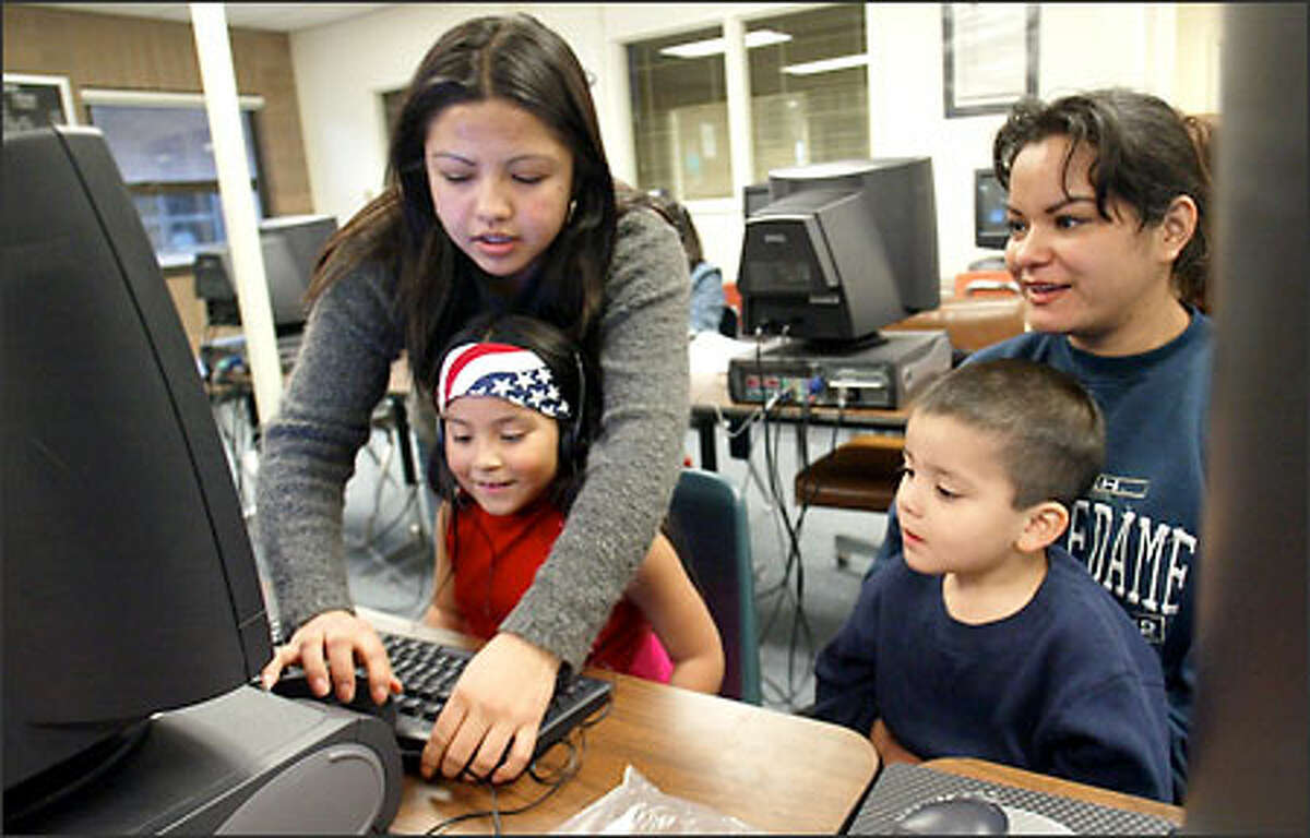 Anlly Cordova, 22, helps Melissa Gamez, 6, Carlos Gamez, 4, their mother, Cinia Sanchez, all originally from El Salvador, during an after-hours English class at Monroe Junior High School. Enrollment of Hispanic students increased more than 1,000 percent at Monroe in the past decade.