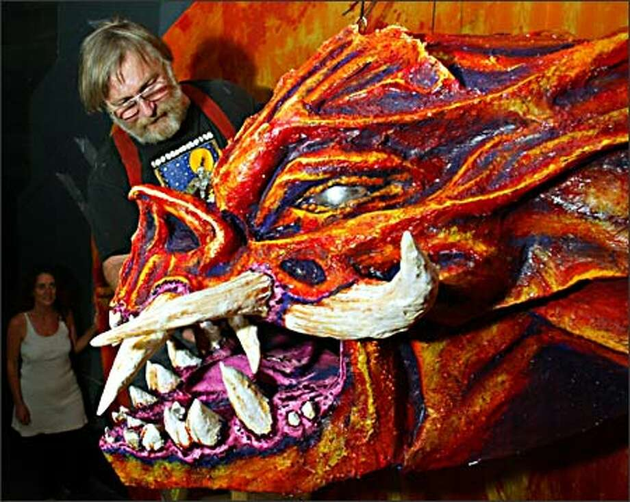 Chuck Nafziger puts Balrog's head in place Wednesday, a toothy addition to the Mines of Moria section of the Middle Earth Ball. Photo: Grant M. Haller, Seattle Post-Intelligencer / Seattle Post-Intelligencer