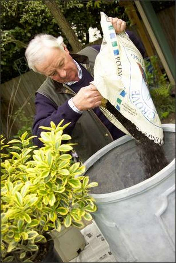 Clematis expert Raymond Evison prepares a large pot for planting with two 1-cubic-foot bags of Cedar Grove potting mix.  Added to the potting soil was a water-holding polymer called Zeba Quench, which is made from cornstarch. It holds water, then releases it, allowing gardeners an extra day between waterings for pots. Photo: Andrew Buchanan