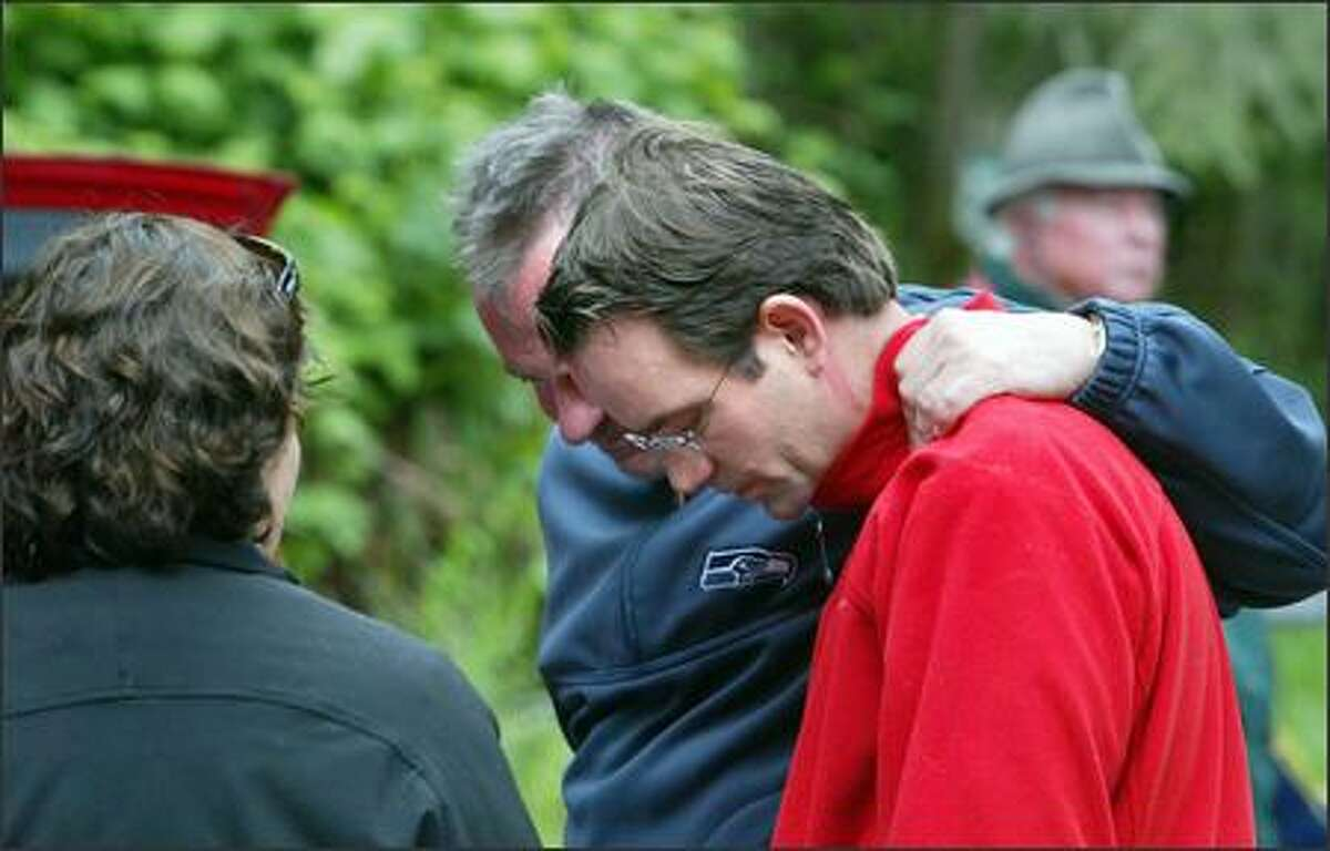 Joe Schreck, brother of the missing man, is comforted by friends and family members as they wait at a Cougar Mountain park trailhead.